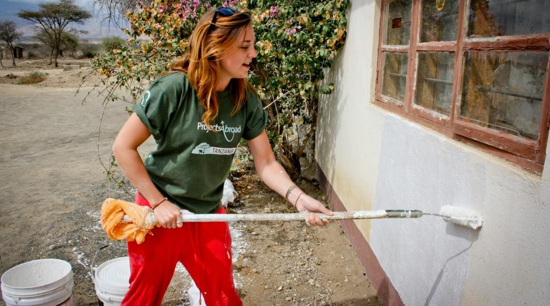 A female volunteer is seen painting a wall as part of her building volunteer work in Tanzania